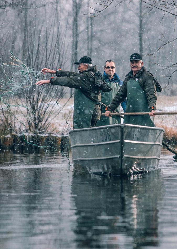 Drei Generationen O Fischer. Großvater Sohn Enkel Fischer. Drei Männer auf einem Fischerboot. Der Großvater wirft das Netz aus. Es ist Winter und es schneit gerade. Kalte Stimmung.
