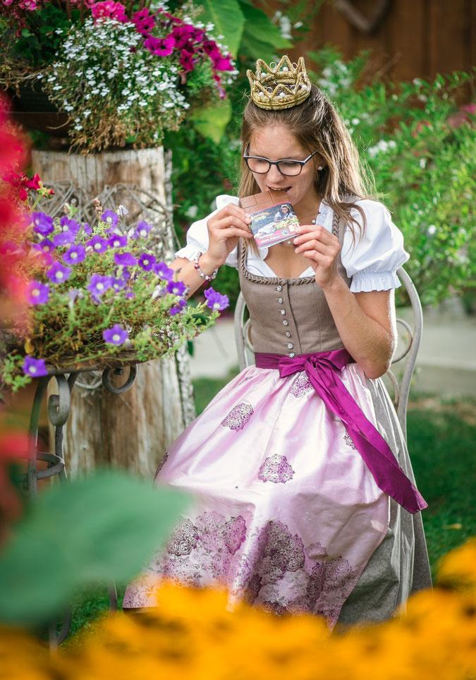 Junge Frau in einem traditionellen Dirndl beißt in eine Schokolade. violettes Kleid, gelbe Blumen im Vordergrund. Violette und grüne Blumen im Hintergrund.