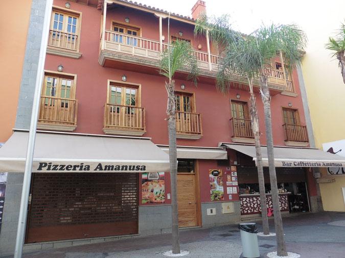 Braunes, kanarisches 2 stockiges Haus mit typischen Balkonen und einer Cafeteria im Eingangsbereich.