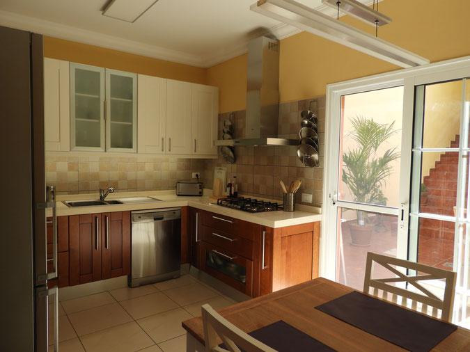 Modern eingerichtete Küche in Holzfarben mit Zugang zur Terrasse.