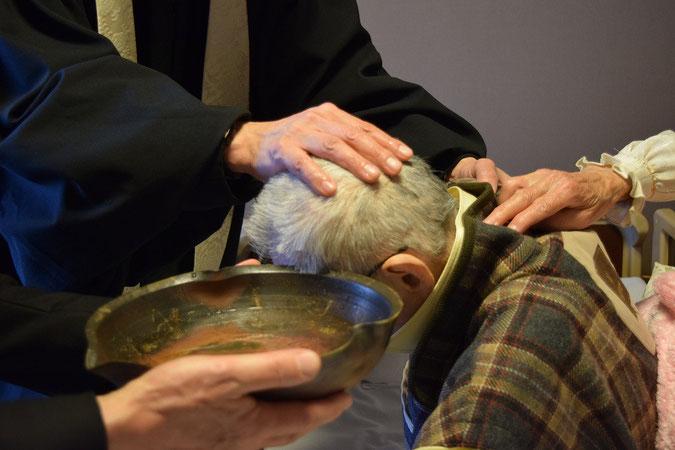 2015年11月23日(月・勤労感謝の日)の午後、高松の居室にて、文彦さんの洗礼式を執り行いました。後ろから支える手は奥さまの史生さん。洗礼盤は泰さんが持ちます。旭東教会の洗礼盤は備前焼の陶芸家・明美さんの作です。