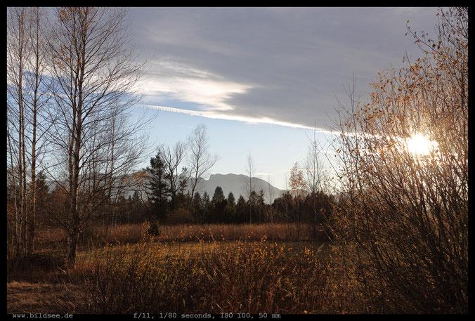 """Endlich sinkt die Sonne unter den Wolkenrand. Benediktenwand mit Attenloher Filze (auch """"Gaißacher Moor"""").."""
