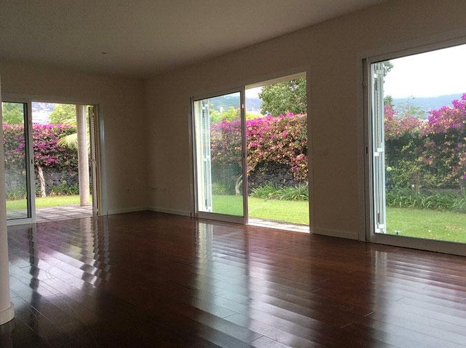 Wohnzimmer mit Parkettboden und Blick in den Garten durch große Terrassentüren.