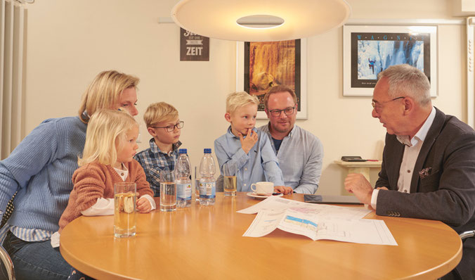 Rainer Mayer mit einem Ehepaar und ihren drei Kindern bei der Finanzierungsberatung zu einem Immobilienkauf oder Immobilienneubau