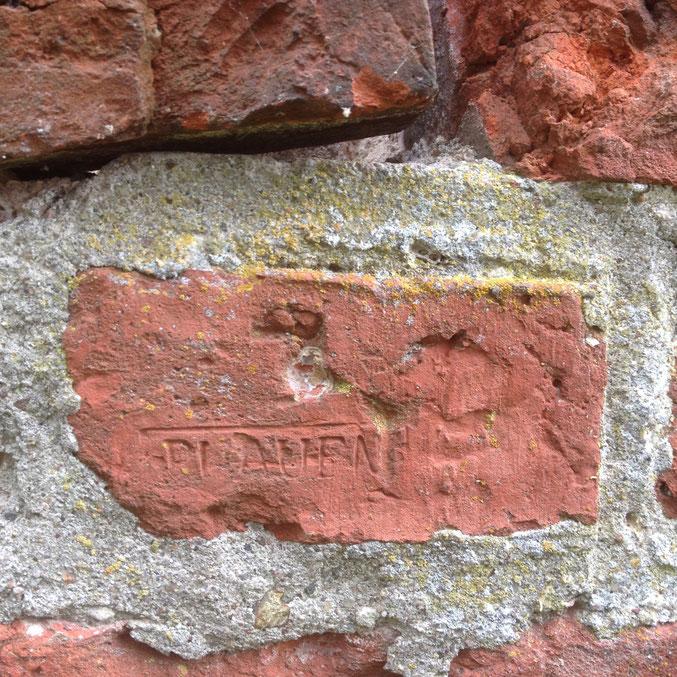 Offensichtlich nachträglich eingemauerter Ziegelstein in das Klingerwerk der Tharauer Kirche. Genauer Fundort unbekannt.
