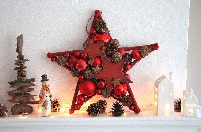 Roter Stern in 50 cm Durchmesser, gefertigt aus roten Glaskugeln, braunen Kokossternen und Zapfen mit Lichterkette dekoriert