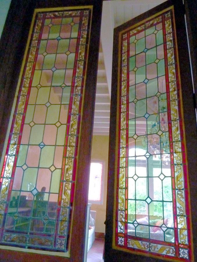 La cage d'escalier s'ouvre sur le séjour, lui-même éclairé par des vitraux.