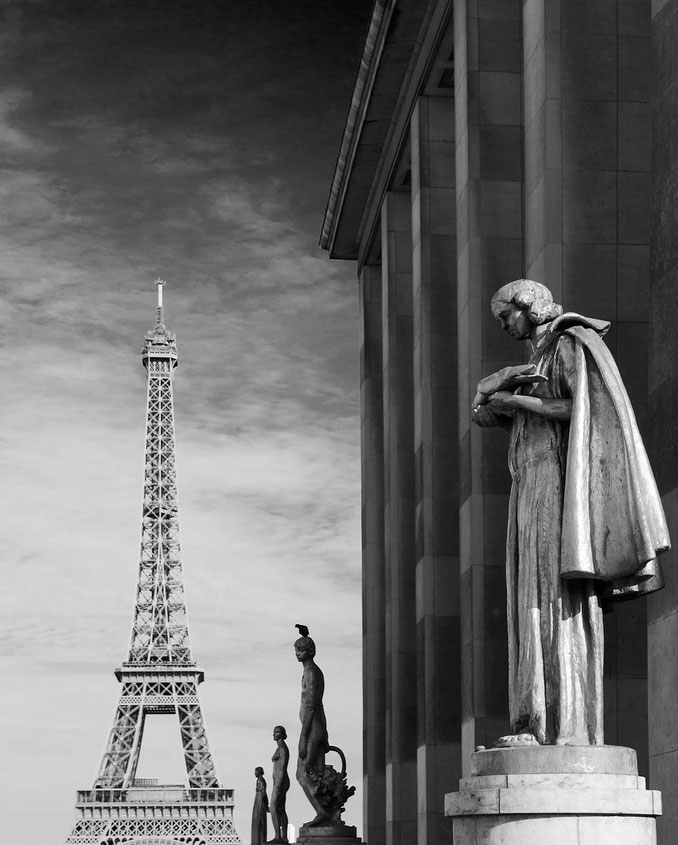 Black and white photograph of stone sculptures in front of the Eiffel Tower, Paris, France
