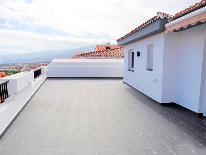 große geflieste Terrasse vor dem Haus mit Meerblick