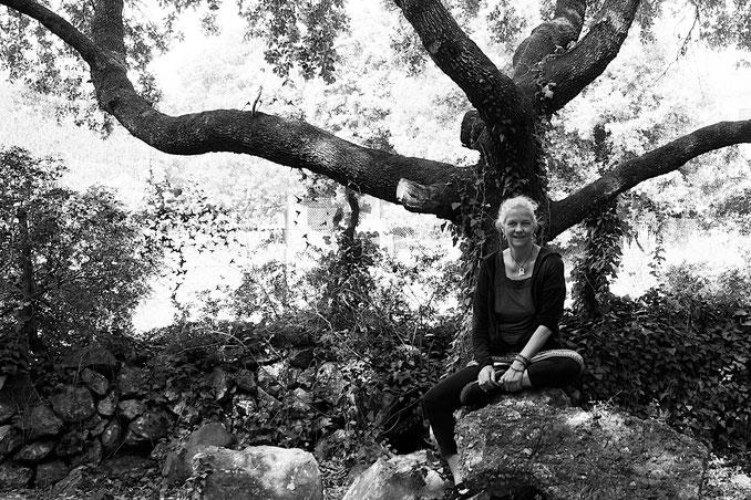 Foto der Trauerrednerin Saskia Leissner-Sager, in der Natur auf einem Stein sitzend