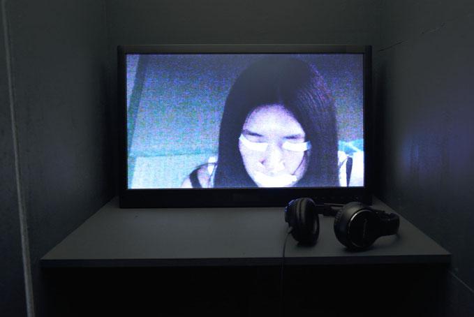 地主麻衣子, 「ようこそ でていけ」13分, モニター・ヘッドフォン・椅子・木材, 2015