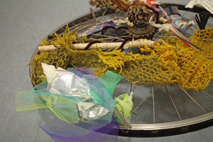 Ein Rad mit Fundstücken aus dem Rhein. Müll wird zu Kunst.