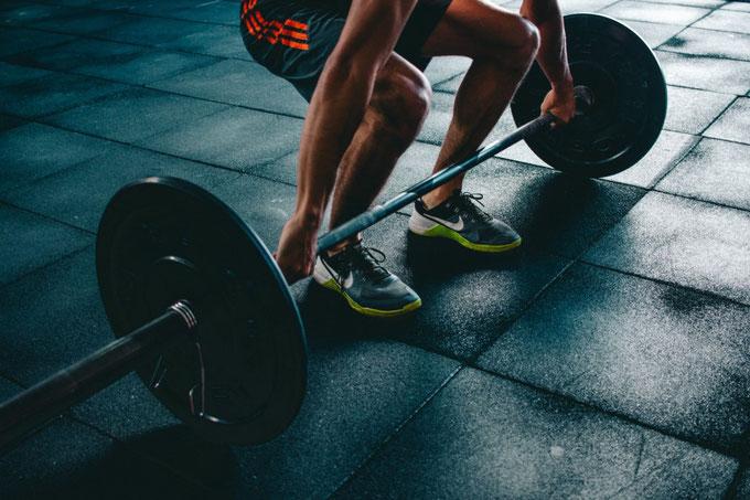 Man sieht den Unterkörper eines Athleten in Sportkleidung, der zum Kreuzheben einer Langhantelstange mit Gewichten ansetzt.