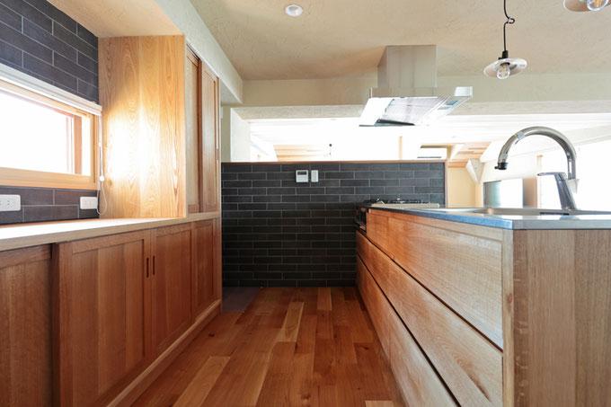 キッチンの壁は落ち着いた色のタイルを張ってシックな雰囲気に