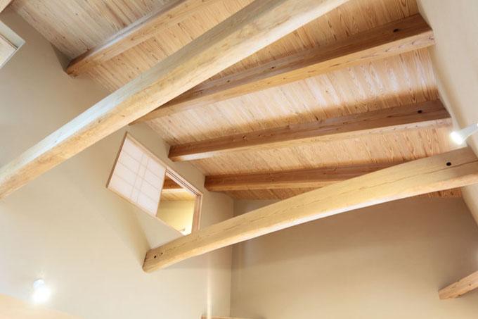 リビング吹き抜けにかかる2本の小屋梁は地松のタイコ丸太