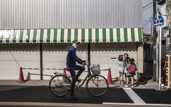 Fahrradfahrer und Kinder auf einer Straße in Enoshima, Japan als Farbphoto