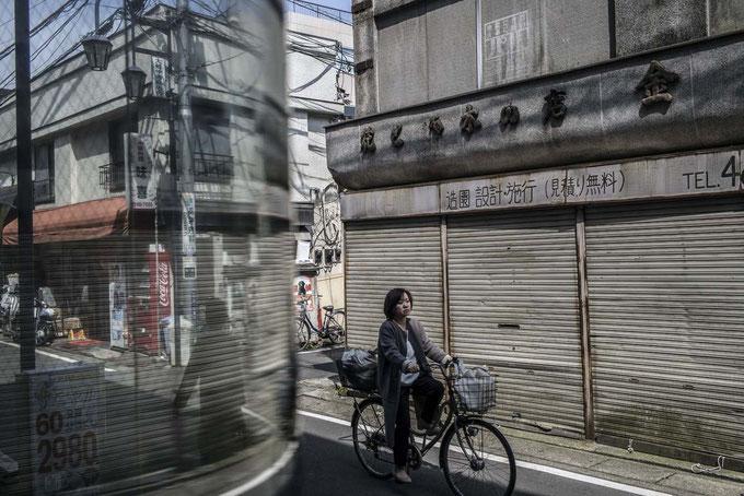 Frau fährt durch die Gassen von Ofuna, Japan als Farbphoto