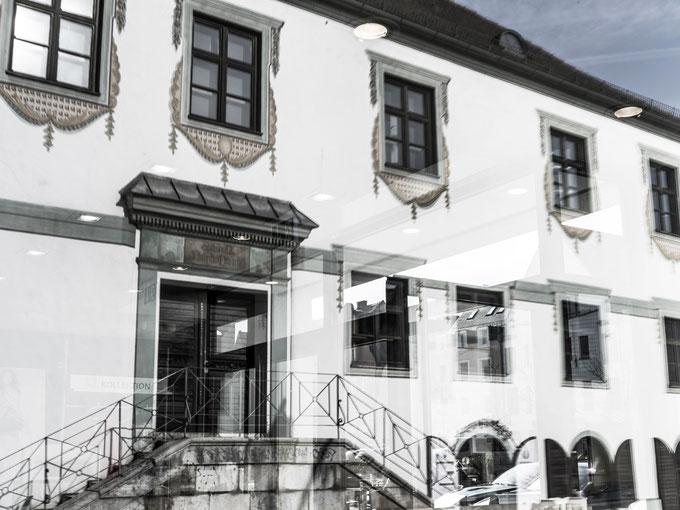Spiegelung des Rentamts in Paffenhofen, Bayern, als Farbphoto