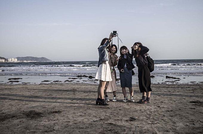 Schülerinnen fotografieren sich gegenseitig auf dem Yuigahama Beach in Kamakura, Japan als Farbphoto