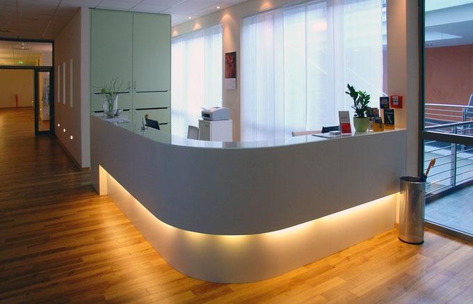 Abgerundete, weiß lackierte Empfangstheke mit indirekter Beleuchtung im Fußbereich