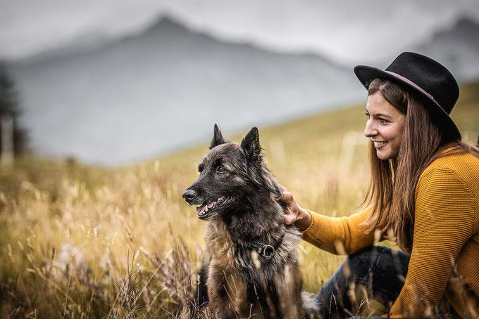 Schäferhund und Halterin mit Fedora Hut auf einer Blumenwiese im Hintergrund Berge festgehalten von der Familien Fotografin Monkeyjolie