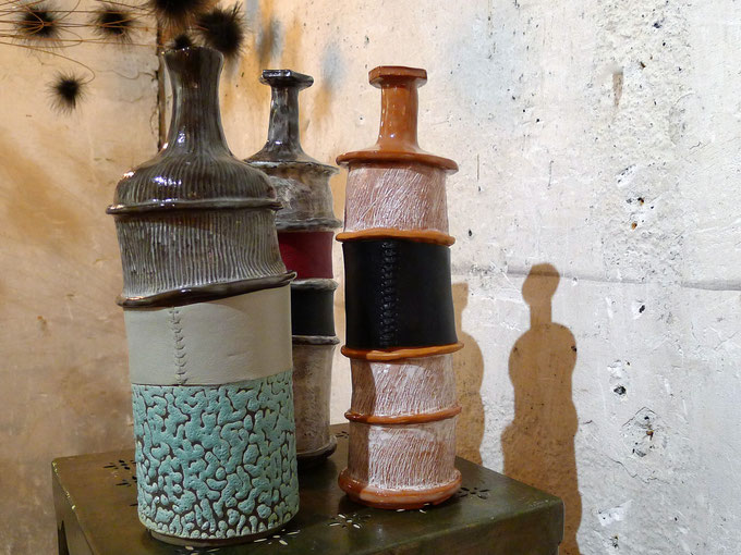 Three unique hand made ceramic bottles with hand-sown reclaimed leather