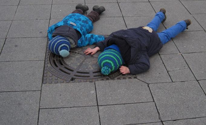 Zwei Kinder, die der Schlagzeug-, Trommel- und Percussionmusik zuhören, die aus dem Gully erklingt