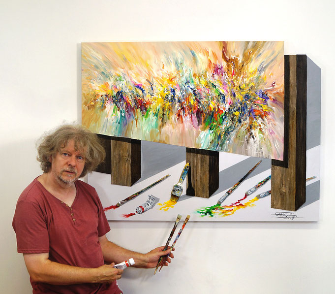 The artist Peter Nottrott in front of his wall sculpture to show the scale