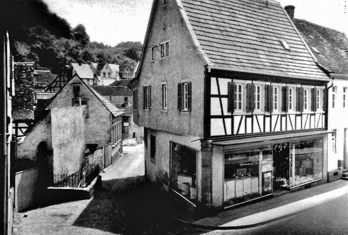 1960,  Ehemaliger Lochbrunnen von der Hauptstrasse aus gesehen. Rechts Haus Profit