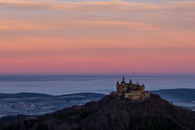 Farbenfroher winterlicher Sonnenaufang; im Hintergrund hat sich in der Nacht Bodennebel gebildet.