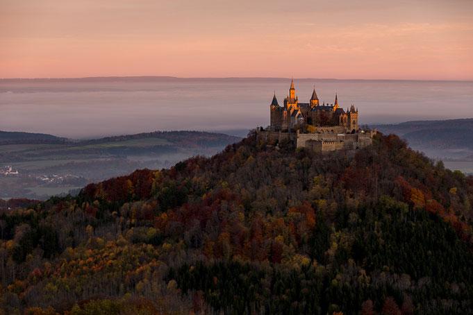 Herbstliche Burg Hohenzollern bei Sonnenaufgang; im Hintergrund leichter Bodennebel.