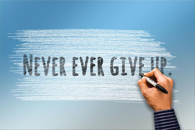 """Eine Hand schreibt """"Never give up"""" auf blauem Hintergrund."""