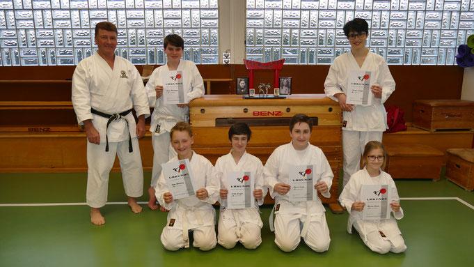 6 erfolgreiche Karatekas nach bestandener Prüfung, zusammen mit ihrem zufriedenen Sensei Michael