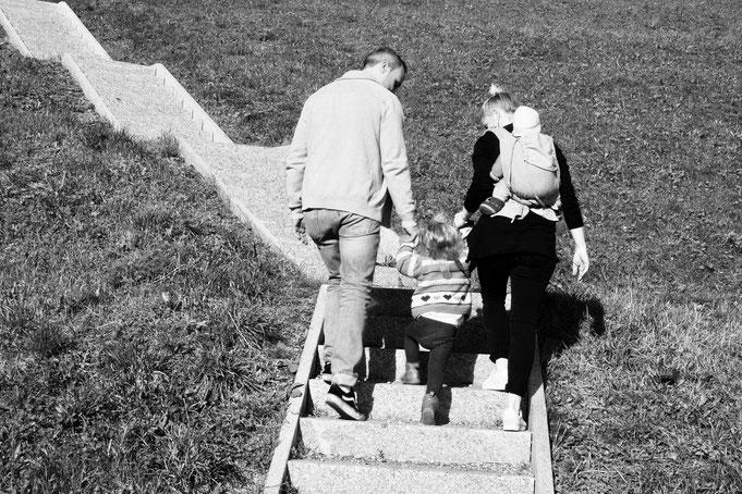 Yogamami und ihre Familie beim Treppensteigen, mit Tragebaby, superaktivem Toddler und ihrem tollen Mann