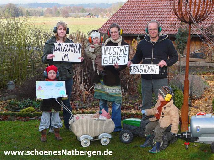 Familie mit Gehörschutz protestiert gegen Industriegebiet
