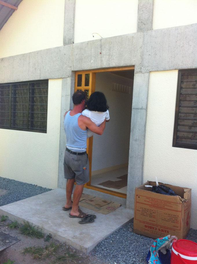 Mann trägt frau über Türschwelle
