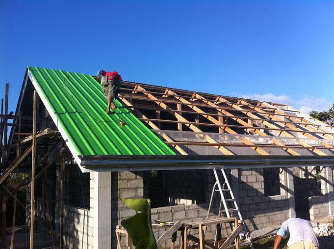 Der Mann auf dem Dach montiert die Aluminiumbleche