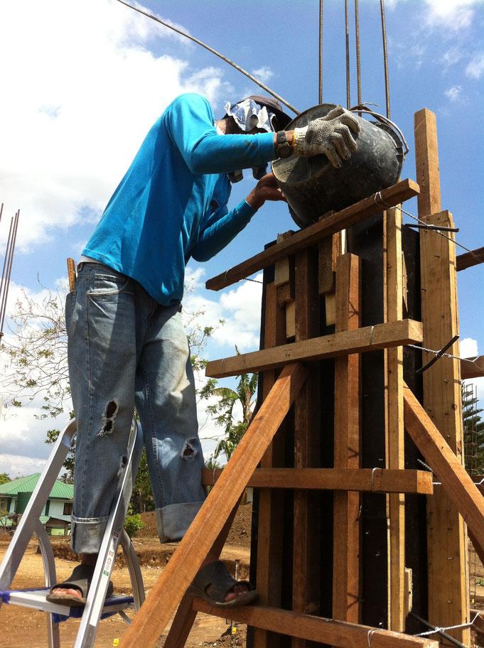 Ein Mann füllt Beton mit Kessel in Pfeilerschalung