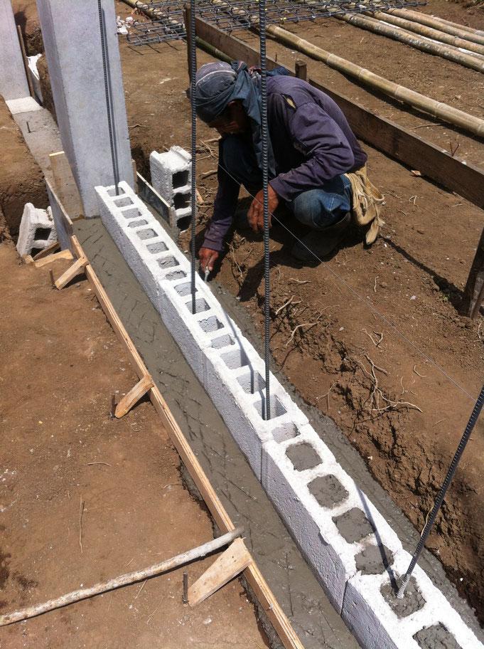 erste Steinreihe mit  Anschlusseisen im frischen Beton wird versetzt