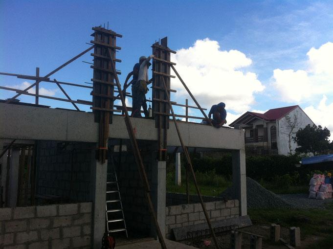 zwei Pfeilerschalungen im Giebel werden von drei Arbeitern gestellt
