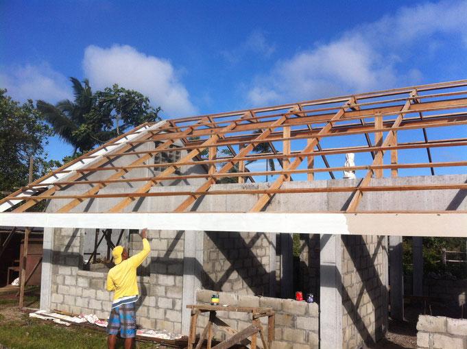 Ein Mann streicht das Stirnbrett beim Dach