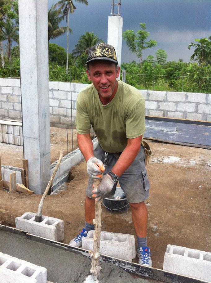 Ein Mann vibriert Beton mit einem Stampfer