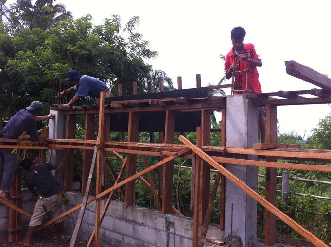 Unterzug wird von vier Männern geschalt mit viel Holz