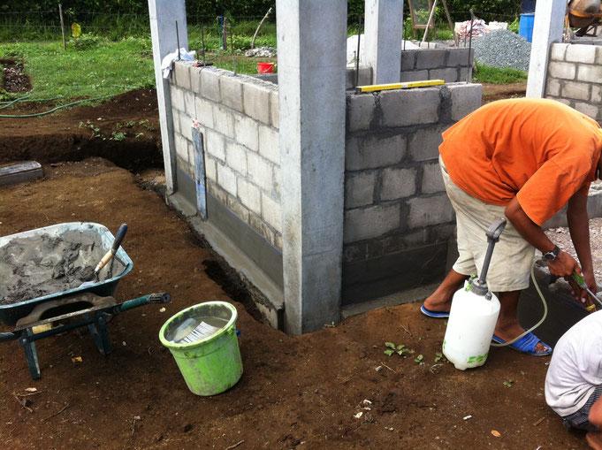 Ein Mann bedient Sprayer für Wasserdichten Aussenputz im Erdreich