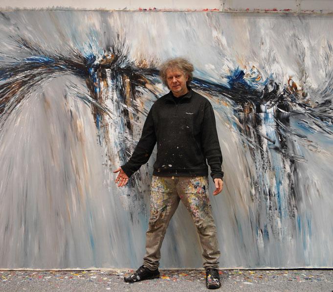 Peter Nottrott vor seinem Gemälde im Atelier, was die 500 x 200 cm veranschaulicht.