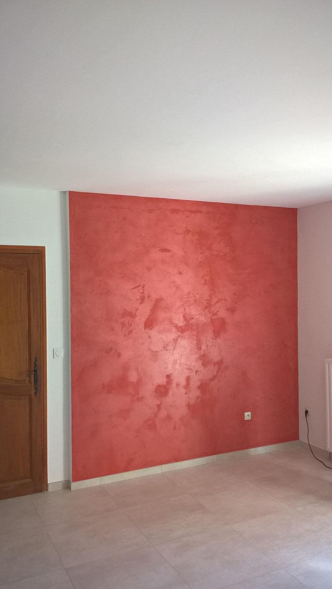 BETON CIRE mural, couleur rouge. Les nuances et effets de matière sont bien visibles et contribuent à l'obtention de la finition minérale recherchée.
