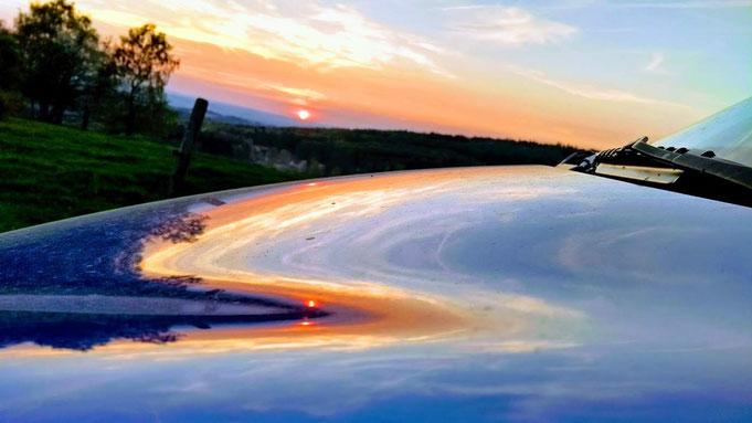 Sonnenuntergang in der Rhön, Spiegelung auf der Motohaube von Helenes Wagen.
