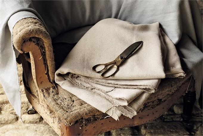 carcasse de fauteuil crapaud, sans tissu, sur lequel on voit la garniture en crin piquée main à l'ancienne comme Ecoute bergère tapissier le pratique. une paire de ciseaux de tailleur est posé sur un tissu plié sur l'assise