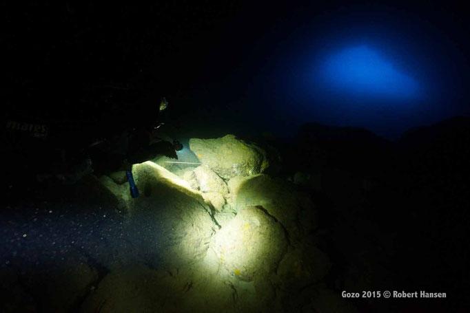 Grotte. Unter dem Stein versteckt sich ein Meeraal vor den Lichtkegeln. © Robert Hansen, Gozo 2015