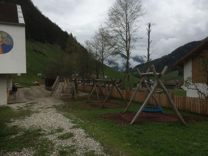 Spielplatz vor dem Kindergarten mit Schaukeln und Rutsche